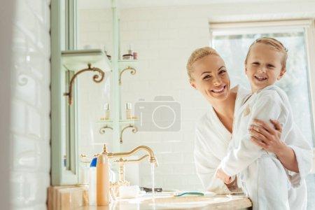 Photo pour Belle mère heureuse en fils portant des robes de chambre et souriant à la caméra dans la salle de bain - image libre de droit