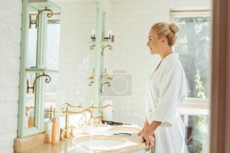 Photo pour Vue latérale de belle jeune femme en peignoir regardant miroir - image libre de droit
