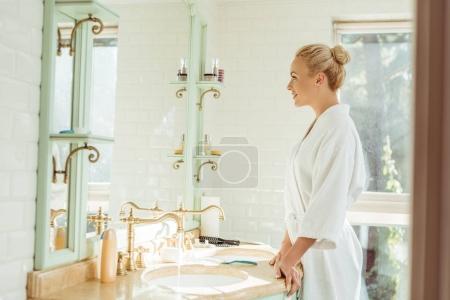 Woman in bathrobe looking at mirror