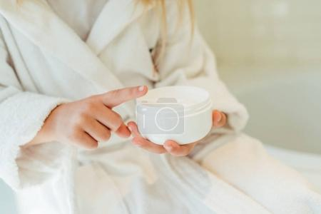 child in bathrobe applying cream