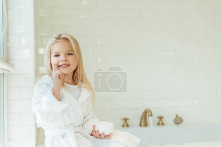 child in bathrobe applying face cream