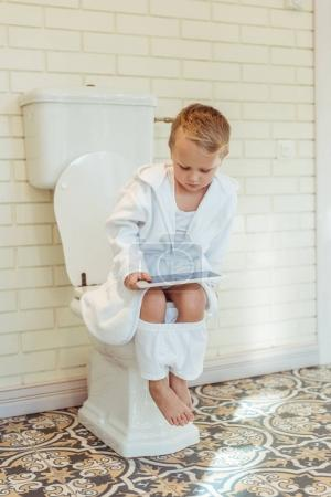 Foto de Niño lindo en ropa interior blanca con tableta digital mientras está sentado en el inodoro - Imagen libre de derechos