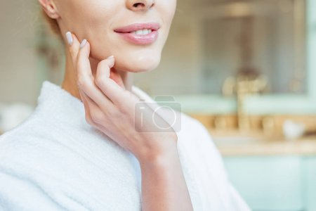 Photo for Cropped shot of beautiful smiling woman in bathrobe touching face with perfect skin - Royalty Free Image