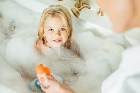 mother washing daughter in bathtub