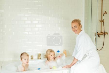 Photo pour Belle mère en peignoir souriant à la caméra tout en lavant les enfants dans la baignoire - image libre de droit