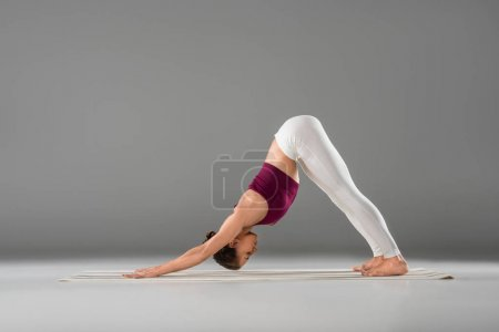 Photo for Side view of athletic girl in sportswear doing yoga stretching exercise on grey - Royalty Free Image