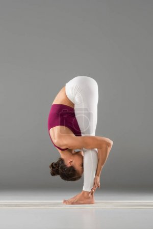Photo for Young woman in sportswear doing yoga stretching exercise on grey - Royalty Free Image