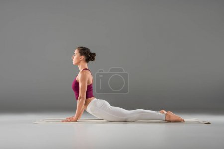 Photo for Side view of girl doing yoga stretching exercise on yoga mat - Royalty Free Image