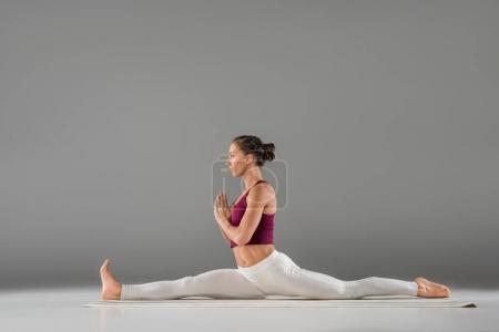 Photo pour Belle jeune femme en vêtements de sport pratiquant le yoga sur gris - image libre de droit