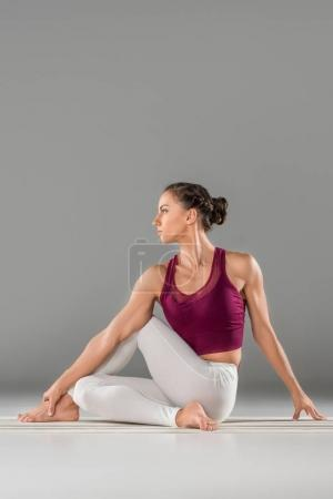 Photo for Woman practicing yoga, sitting in Half lord of the fishes exercise, Ardha Matsyendrasana pose - Royalty Free Image