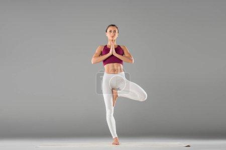 Photo pour Femme pratique l'yoga, debout dans l'exercice de l'arbre, Vrksasana pose - image libre de droit