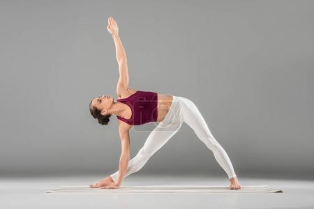 Photo for Woman practicing yoga, standing in Extended Side Angle exercise, Utthita parsvakonasana pose - Royalty Free Image