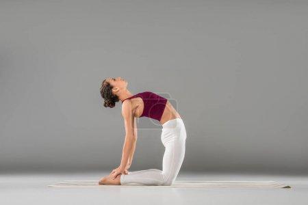 Photo pour Jeune femme pratiquant l'yoga, assis dans l'exercice de chameau, Ustrasana pose - image libre de droit