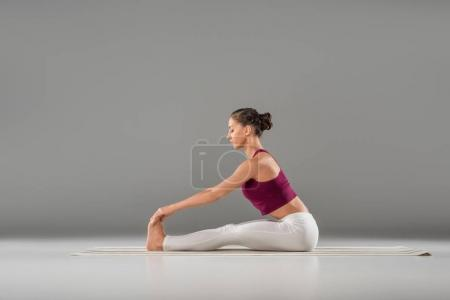 Photo for Full length side view of young woman in sportswear practicing yoga on grey - Royalty Free Image
