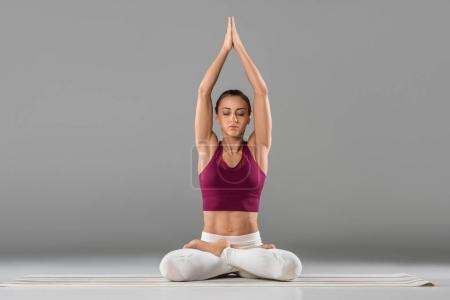 Photo pour Jeune femme avec des yeux fermés, méditation en posture de lotus en gris - image libre de droit