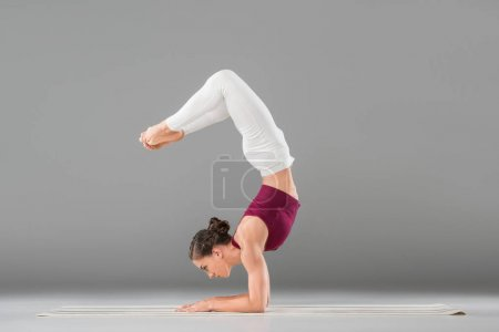 Photo for Young woman performing yoga headstand with bent legs pose - Royalty Free Image