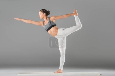Photo for Full length view of beautiful young woman in sportswear practicing yoga - Royalty Free Image