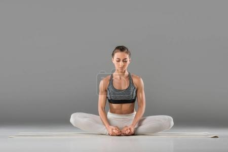 Photo for Attractive sporty young woman performing lotus pose - Royalty Free Image