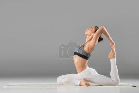 Photo for Side view of young woman practicing one legged pigeon yoga pose - Royalty Free Image
