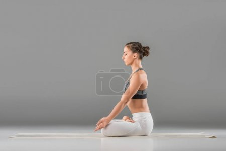 Photo for Beautiful young woman performing lotus pose on grey - Royalty Free Image