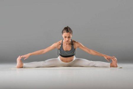 Foto de Atractivo joven practicando gran angular sentado dóblese hacia adelante yoga pose - Imagen libre de derechos