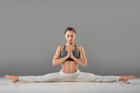 Photo for Woman practicing wide angle seated forward bend yoga pose - Royalty Free Image