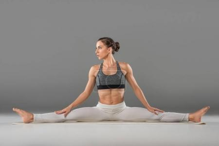 Photo for Young woman practicing wide angle seated forward bend yoga pose - Royalty Free Image