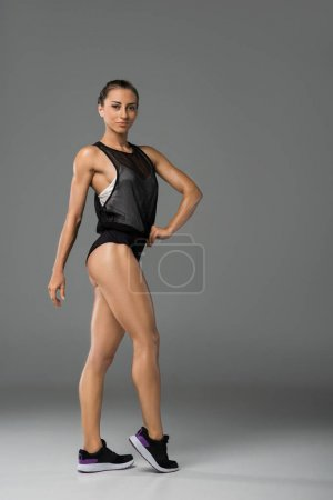 Photo for Athletic confident young woman in sportswear looking at camera isolated on grey - Royalty Free Image