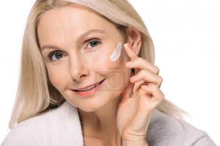 Photo pour Souriant femme mûre appliquer crème cosmétique isolé sur blanc - image libre de droit