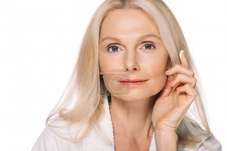Photo for Beautiful mature woman applying cosmetic cream isolated on white - Royalty Free Image