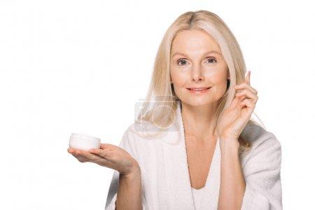 mature woman applying cosmetic cream