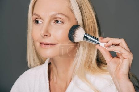 Photo for Close-up portrait of mature woman doing makeup isolated on grey - Royalty Free Image