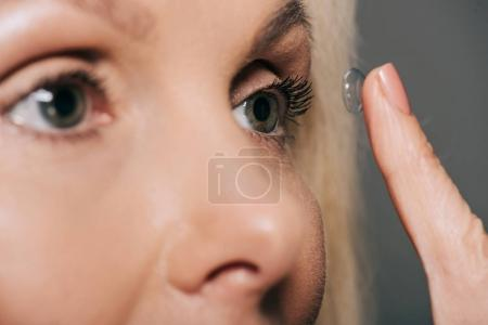 Photo for Close-up view of woman applying contact lens isolated on grey - Royalty Free Image