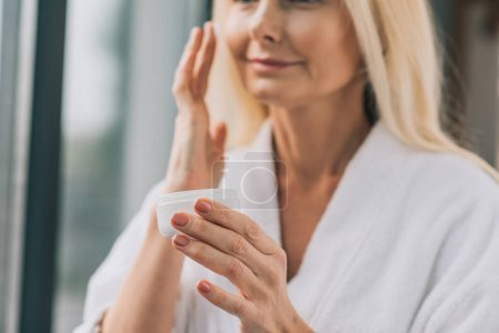 Photo for Beautiful mature woman in bath robe applying cosmetic cream - Royalty Free Image