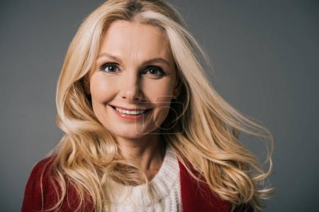 Photo for Happy mature woman with beautiful waving hair isolated on grey - Royalty Free Image