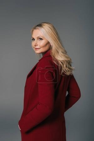 Photo pour Femme mûre à la mode en manteau rouge à la recherche retour isolé sur fond gris - image libre de droit