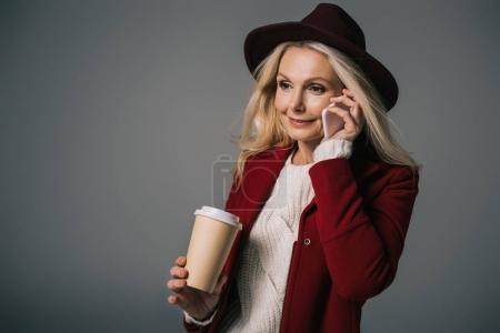 Photo for Mature woman with paper cup of coffee talking by phone isolated on grey - Royalty Free Image