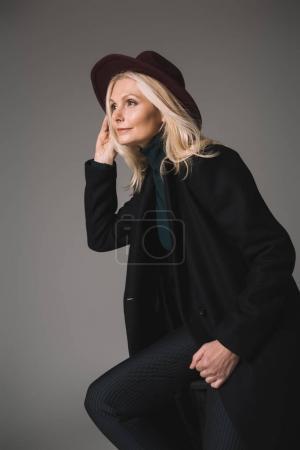 Photo pour Belle femme mature en manteau et chapeau isolé sur gris - image libre de droit