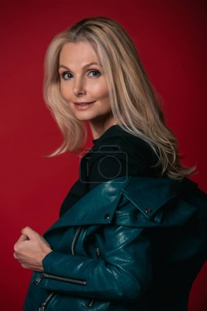 mature woman taking of leather jacket
