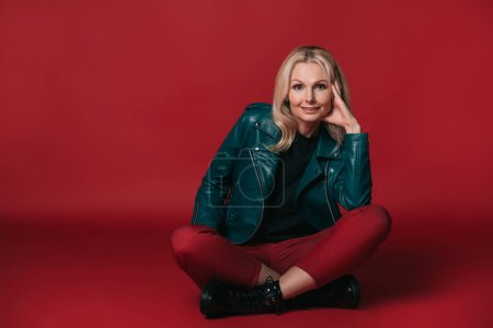 Photo for Stylish mature woman sitting on floor on red background - Royalty Free Image