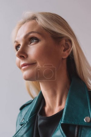 Photo pour Close-up portrait of smiling mature woman looking away isolated on grey - image libre de droit