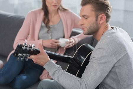 Photo pour Petit ami joue la chanson à la guitare acoustique à sa petite amie à la maison - image libre de droit