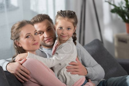 Parents hugging daughter
