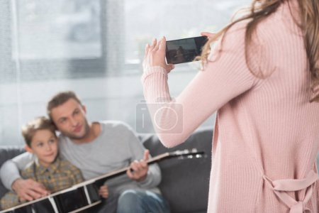 Photo for Mother taking photo of father with son and guitar - Royalty Free Image