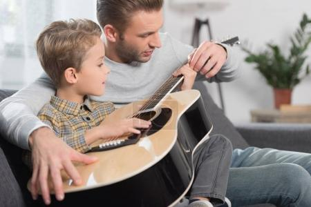 Father teaching son play guitar
