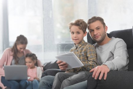 boy and father using digital tablet