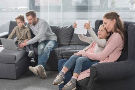 Foto de Familia joven con dos niños sentados en el sofá en la sala de estar y utilizando varios dispositivos digitales - Imagen libre de derechos