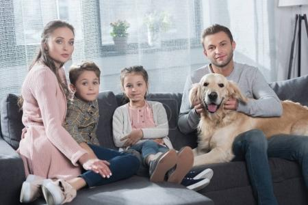 Family petting dog on couch