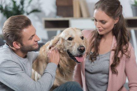 Couple petting dog