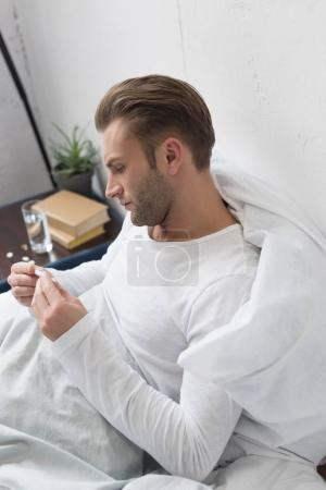 sick man looking at thermometer